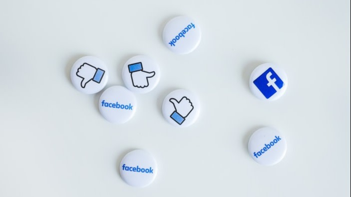 8 facebook buttons with the word, logo and thumbs up placed on white table