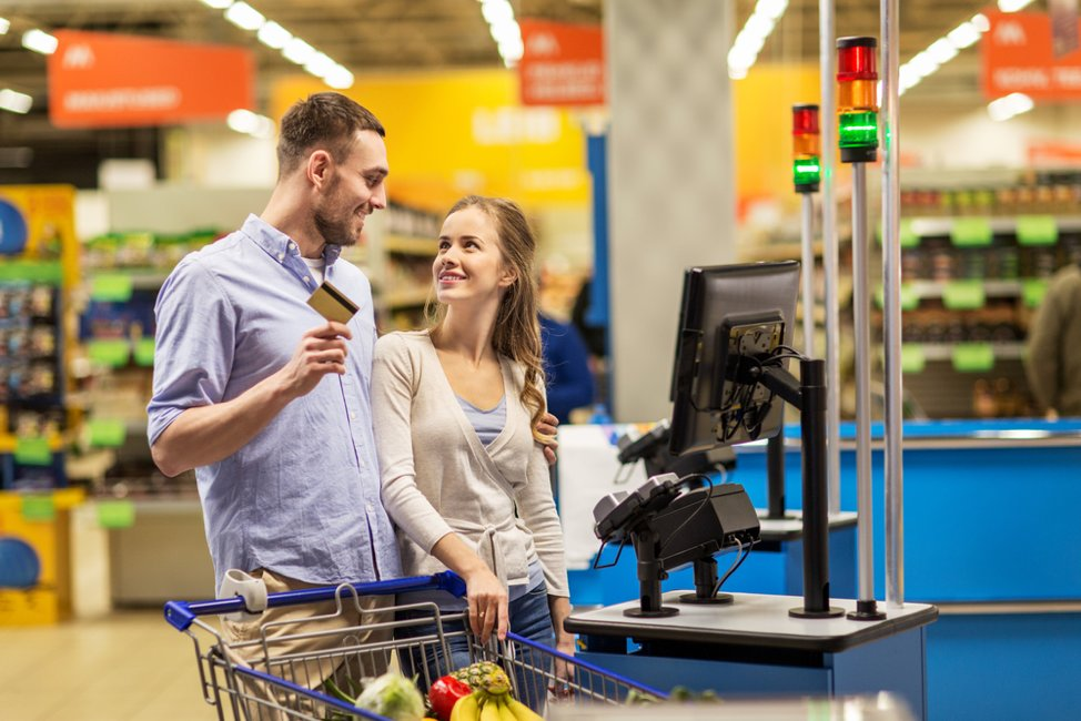 A man and woman happily use their card to buy groceries.