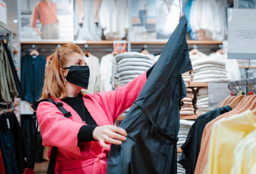 A woman wearing a black face mask looks at an item of clothing in a clothing store.