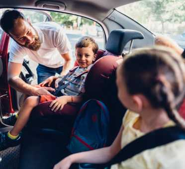 Shine Lawyers | Parent strapping children into car seats | Shine Lawyers