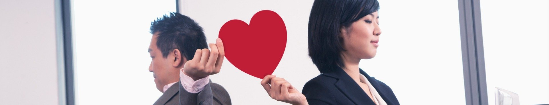 Shine Lawyers | Work romance between two business people holding a heart | Shine Lawyers