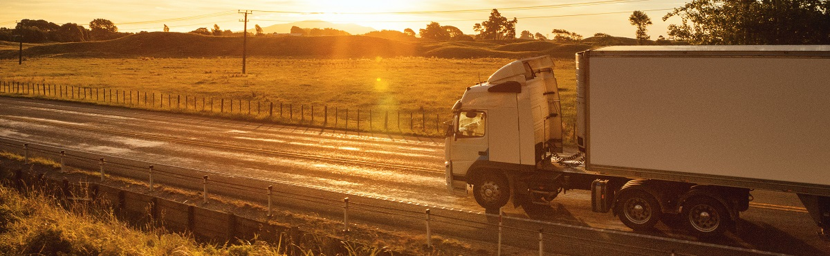 Shine Lawyers | Semi-truck at sunset traveling through the rural landscape of New Zealand