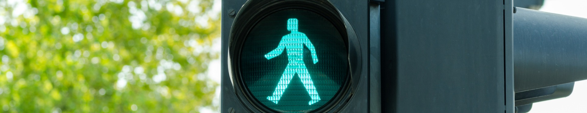 Shine Lawyers | Green traffic light for pedestrians on the crosswalk
