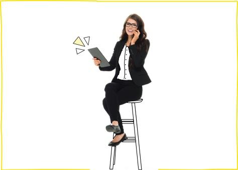 Mujer joven vestida de ejecutiva sentada hablando por teléfono y navegando en su Tablet gracias a una de nuestras tarifas de fibra y móvil para negocios