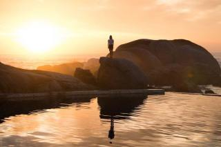 girl-in-the-sunset-on-some-rocks-on-the-water