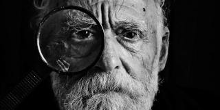old-man-portrait-with-magnifying-glass-close-up-shot