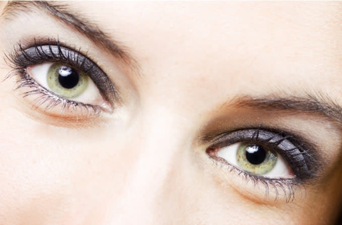Closeup image of a woman's bright green eyes