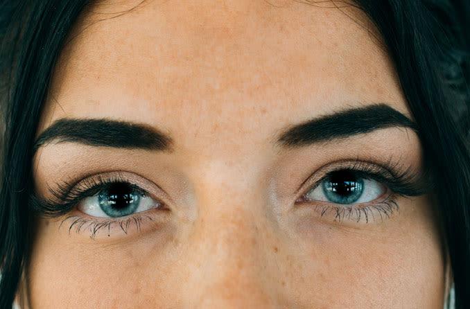 Donna con capelli neri e occhi blu con pupille dilatate