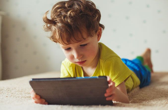 A child staring at a tablet screen while in bed.