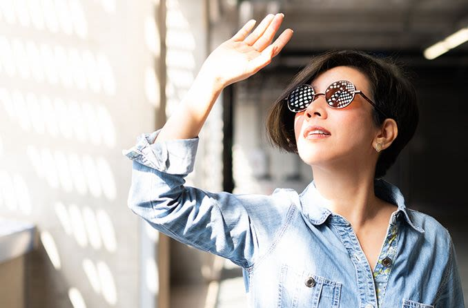 woman wearing uv protected sunglasses shielding her eyes from sun