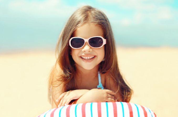 Ребенок защищает глаза, надевая солнцезащитные очки Rebenok zashchishchayet glaza, nadevaya solntsezashchitnyye ochki