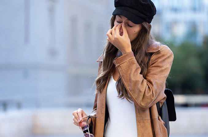 woman allergic to her sunglasses rubbing bridge of nose