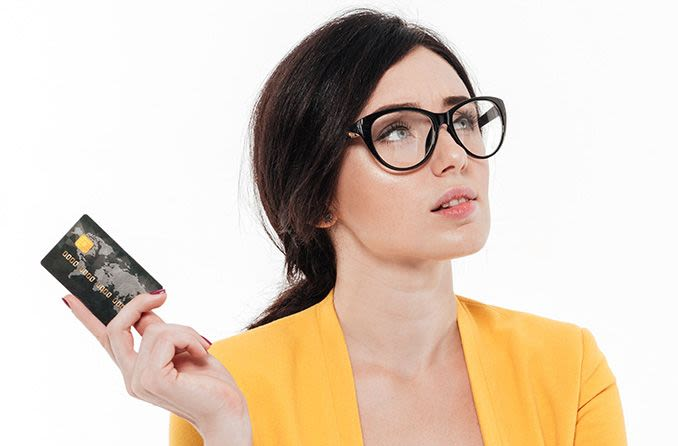 Woman with eyeglasses holding a credit card looking perplexed
