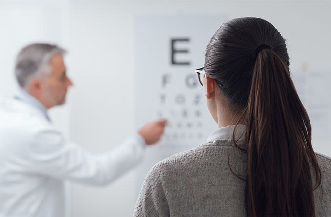 woman with astigmatism looking at eye chart wanting to get lasik surgery
