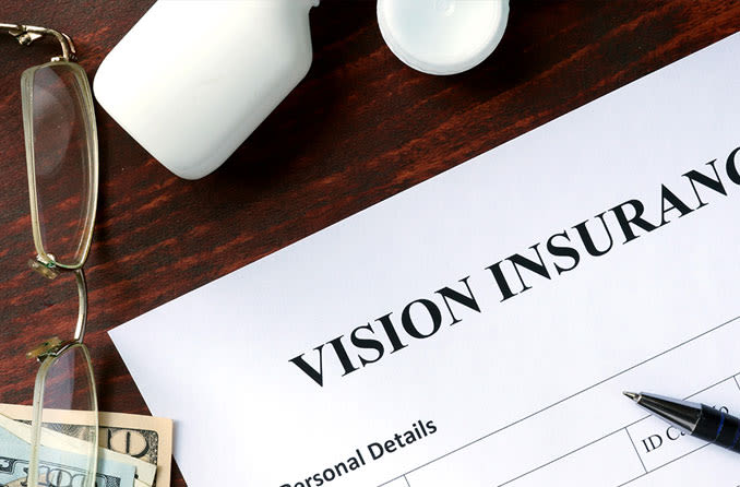 vision insurance form on desk next to reading glasses and cash