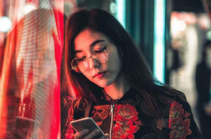 鼻にかかっている眼鏡フレームを持つ女性