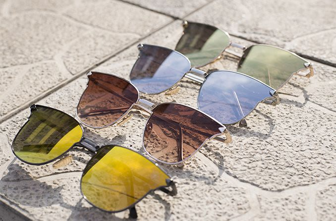 different colored sunglass lenses on concrete