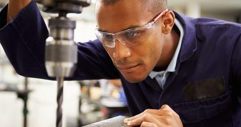 homme portant des lentilles en polycarbonate tout en travaillant avec des outils