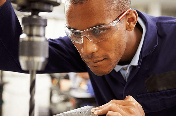 Homem utilizando lentes de policarbonato ou orgânicas para trabalhar na indústria.