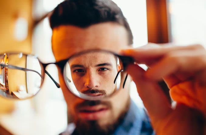 Mann schaut durch Brillenglas