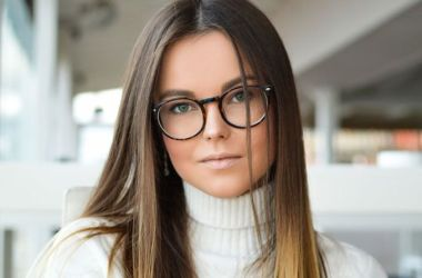 Young woman in sweater and glasses