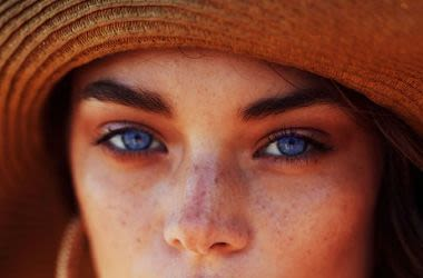 Woman wearing hat with blue eyes.