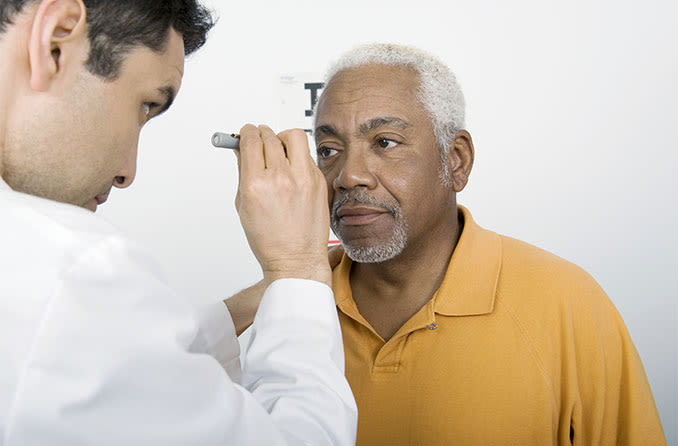 eye doctor looking at man's eye with cataracts