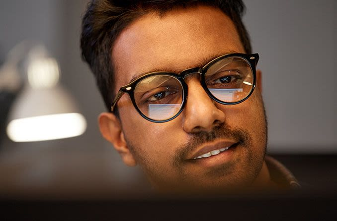 man wearing eyeglasses with computer screen in reflection of eyeglass lenses