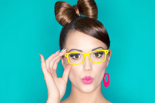 Woman with a heart shaped face wearing yellow wayfarer glasses