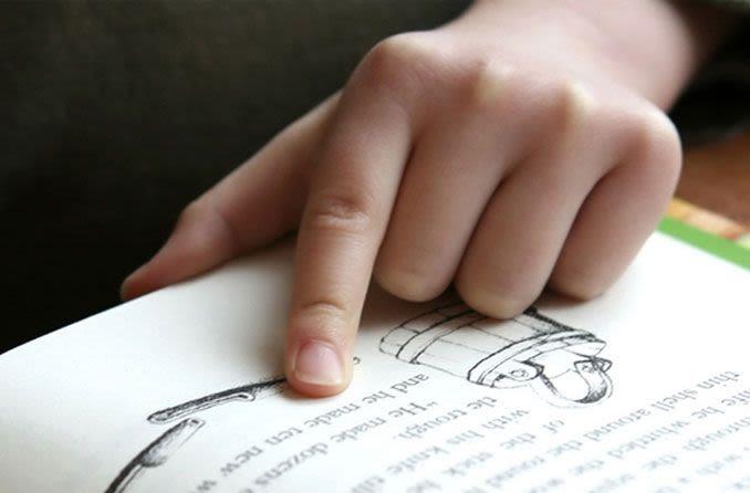 Kind liest mit seinem Finger