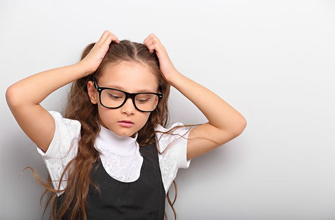 young girl wearing eyeglasses with a headache
