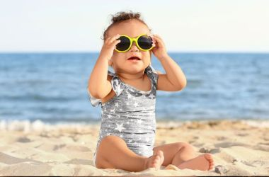 Baby on the beach, wearing sunglasses.