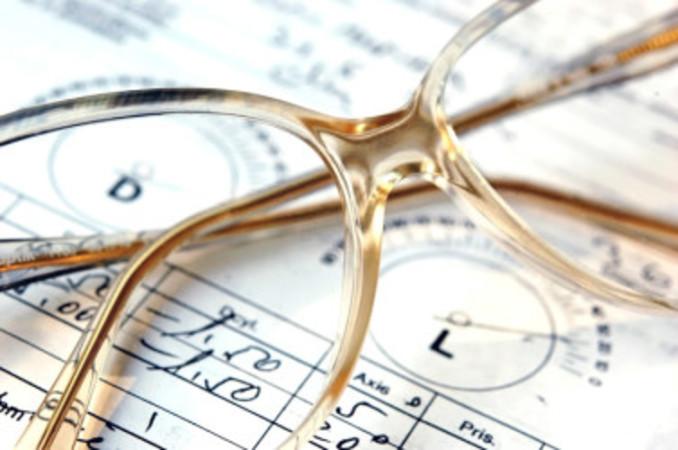 चश्मे का एक जोड़ा एक चश्मा पर्चे के ऊपर।