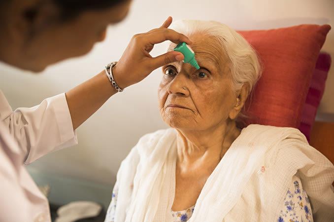 Un'infermiera che applica gocce oculari per la cataratta agli occhi di un paziente anziano.