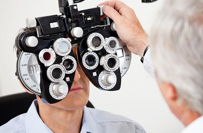 man receiving a refractive eye exam from optometrist