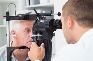 Elderly man receiving eye examination.
