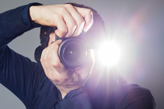 Man taking a picture with a camera flash