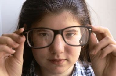 Girl holding up glasses and peering through lenses
