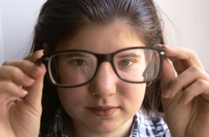 Gözlüklerini tutan ve lenslerin arasından bakan kız