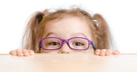 girl with glasses peeking over a desk