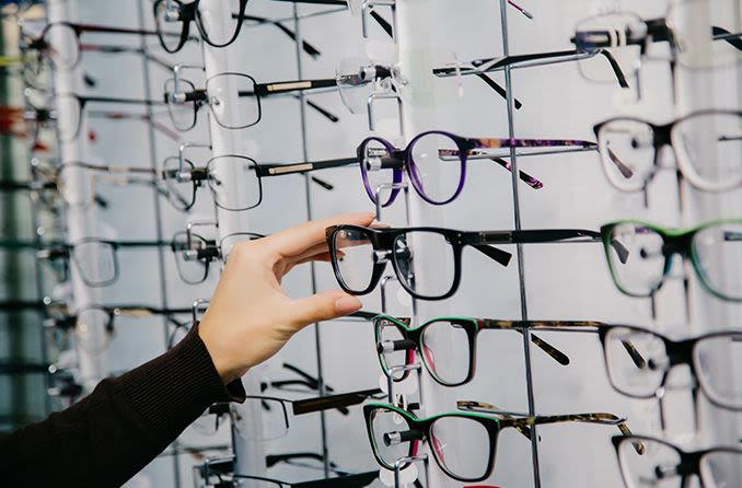 Woman choosing a pair of eyeglasses from the display