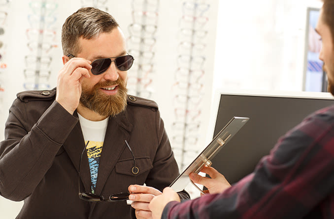 man trying on prescription sunglasses in optical store