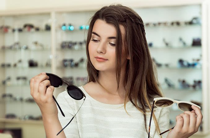 woman shopping for sunglasses trying to decide between metal or plastic framed sunglasses
