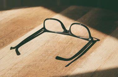Óculos descansando em uma mesa.