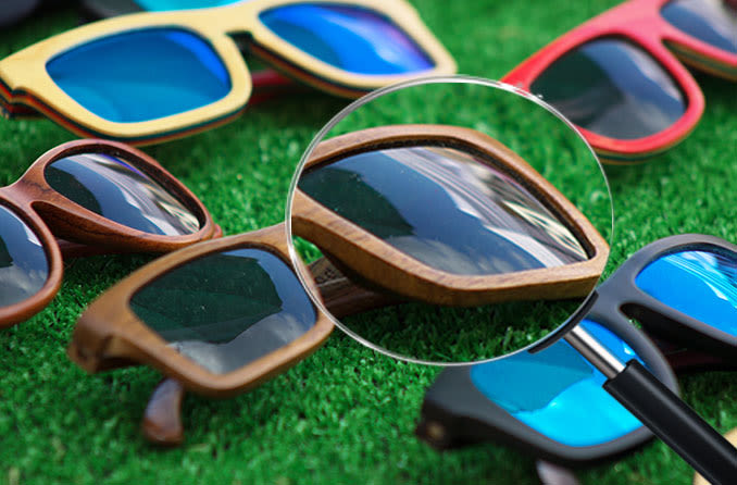 Multiple pairs of wayfarer sunglasses on green turf