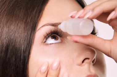 Woman putting eye drops into eye