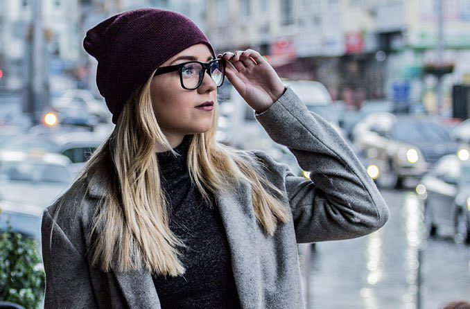 Mujer sosteniendo sus anteojos y mirando hacia el horizonte.