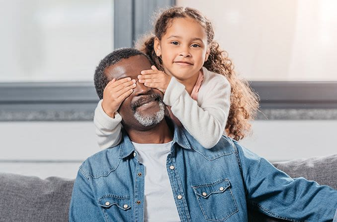 Junges Mädchen mit Händen über den Augen des Vaters