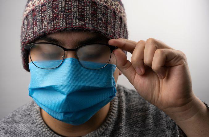 चेहरे का मुखौटा पहने एक आदमी पर धूमिल चश्मा