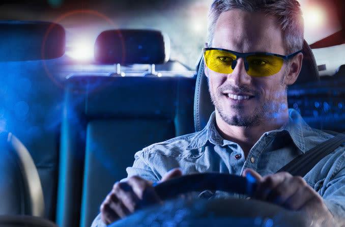 Uomo che indossa occhiali da guida notturna durante la guida
